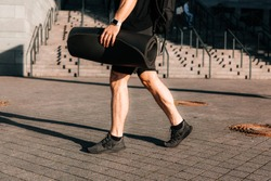 Tired and satisfied male sportsman returns home after morning workout. Cut view of sporty man's legs. Urban sport concept. Man walking on street and holding rolled yoga mat.