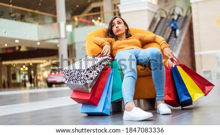 Tired and stressed young woman is lying and resting in the chair  with many shopping bags in the mall
