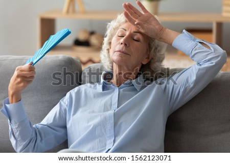 Tired annoyed senior woman holding waving fan feel hot sit on sofa at home without air conditioner, overheated exhausted old elder grandma sweating suffer from hormone problem summer heat concept