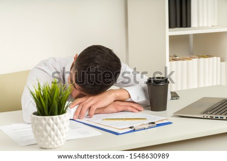 Tired asian businessman sleeping in office. Middle eastern business man worked late and fell asleep on the table. Creative casual gay sleeping at his working place, woke up.
