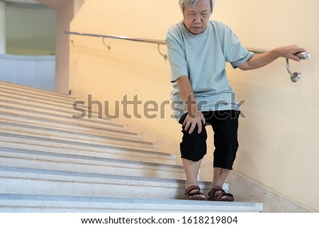 Tired asian senior woman going down the stairs with leg pain,touch her knee pain,female elderly with acute knee joint pain,physical injury,exhausted old people suffer from gout,arthritis,rheumatism