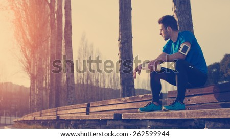 Tired athlete resting on the bench in park with bottle of water, armband with mobile phone and listening music (intentional sun glare and vintage color)