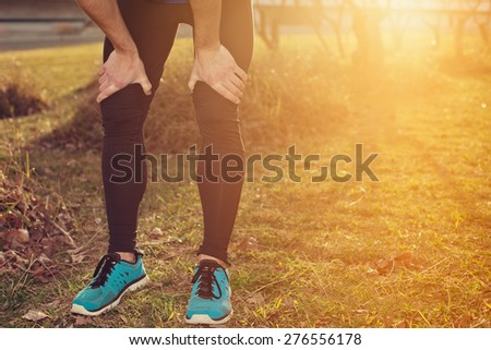 Tired athlete standing in park at sunset and resting (intentional sun glare)
