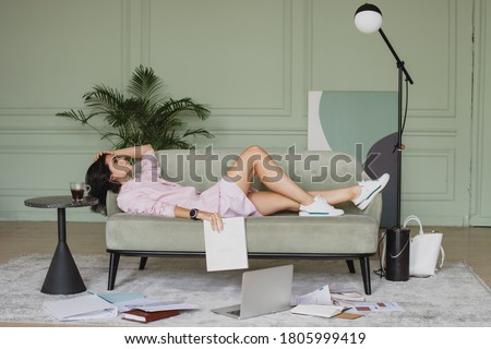 Tired beautiful business woman lying down on the sofa. Foto stock ©