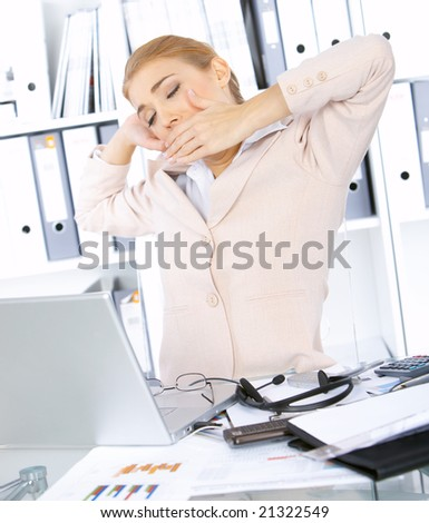 Tired beautiful business woman yawning in office