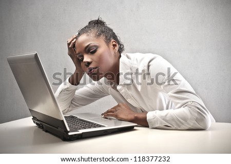 Tired black woman in front of a computer