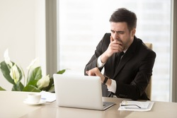 Tired bored businessman yawning at workplace near laptop, looking at wristwatch, checking time, boring work, dead end job, overwork extra after hours, lack of sleep, insomnia consequences, need rest