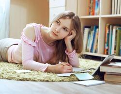 Tired bored teenage schoolgirl feeling headache or fatigue doing homework at home.