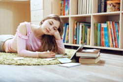 Tired bored teenage schoolgirl feeling headache or fatigue doing homework at home. Online education, E-learning concept. Distance communication with gadget