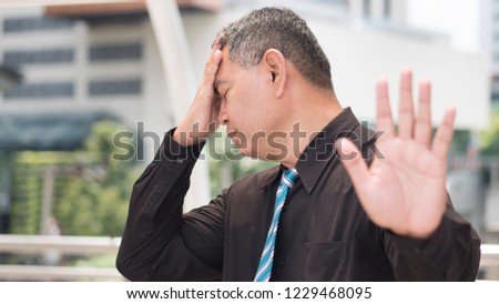 tired business man saying no. portrait of exhausted, tired asian businessman showing stop, halt hand gesture headache. 50s old southeast asian man model