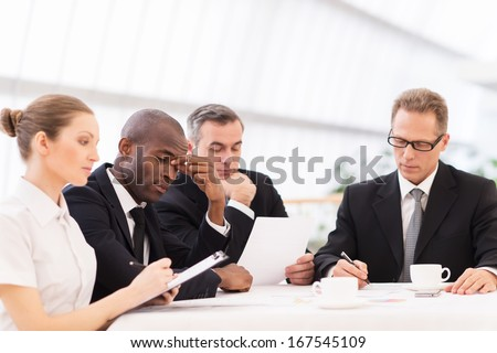 Tired business people. Four business people in formalwear looking tired while sitting together at the table