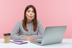 Tired business woman having fun making fish lips sitting at laptop on workplace, making ridiculous grimace feeling guilty and confused. Indoor studio shot isolated on pink background