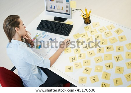 tired business woman with adhesive notes on table. High angle view