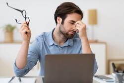 Tired Businessman Holding Eyeglasses And Massaging Nosebridge Suffering Headache And Eyes Fatigue After Work At Laptop Computer Sitting In Modern Office. Selective Focus
