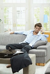 Tired businessman resting on couch at home after long day of work.