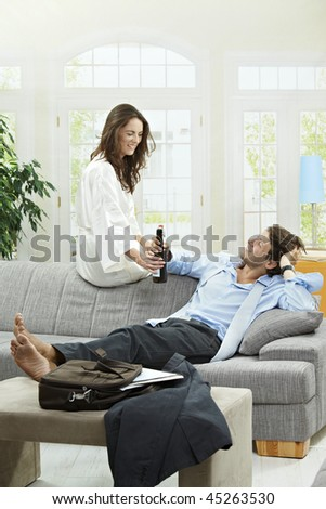 Tired businessman resting on couch at home after long day of work. Woman giving him bottle of beer.