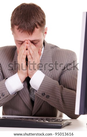 tired businessman sitting at a computer on a white background