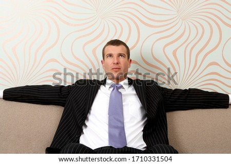 Tired businessman sitting on sofa