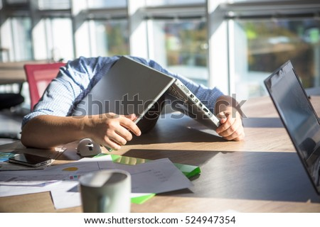 Tired businessman sleeping after hard working day in office interior. Man lying on table with laptop computer on. Business concept.