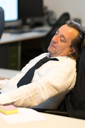 Tired businessman sleeping at his desk during work break