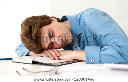 Tired Businessman Sleeping At Workplace In The Office