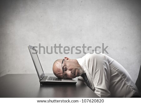 Tired businessman sleeping on his laptop's keyboard