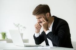 Tired businessman squinting eyes looking at laptop screen trying to focus concentrate, office employee thinking of online problem suffering from fatigue, headache or bad sight, computer syndrome