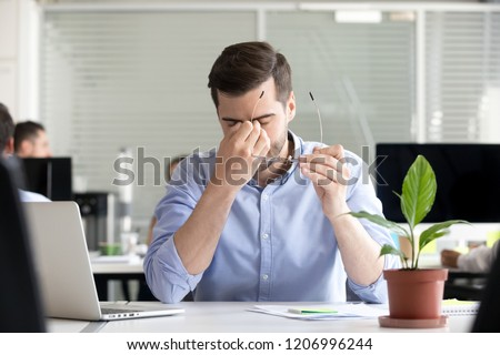 Tired businessman taking off glasses lost productivity after office work laptop use to relieve dry irritated eyes feeling fatigue tension or strain, chronic computer syndrome, bad weak vision problem