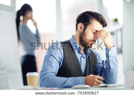 Tired businessman touching his forehead while sitting by workplace in front of computer monitor