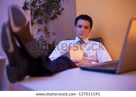 Tired businessman trying to stay awake while eating chinese food late at night in the office