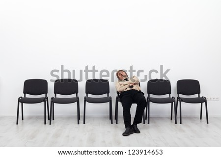 Tired businessman waiting - sitting on a chairs row