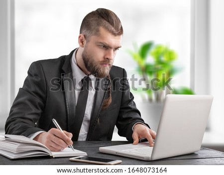 Tired businessman working with laptop pc