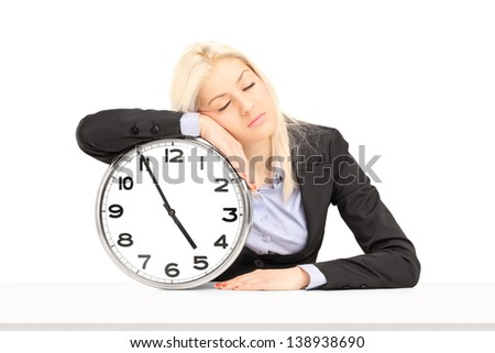 Tired businesswoman sleeping on a wall clock at workplace, isolated on white background