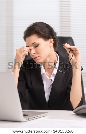 Tired Businesswoman. Tired Middle-Aged Businesswoman Sitting At Her Working And Keeping Her Eyes Closed