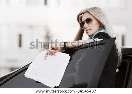 Tired businesswoman with a car