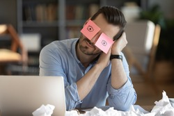 Tired Caucasian male worker fall asleep at workplace in office, have sticker pads on eyes. Exhausted young man take nap doze off sleep at desk, overwhelmed with work. Fatigue, exhaustion concept.