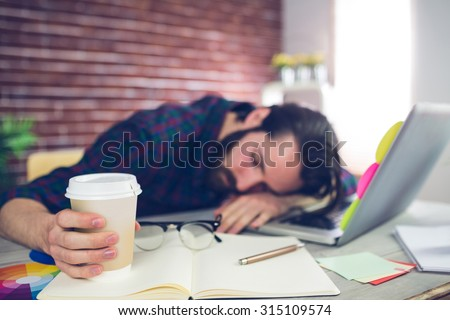 Tired creative editor holding disposable cup while sleeping on office desk