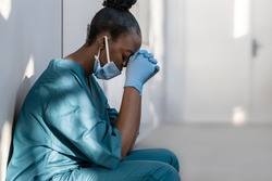 Tired depressed female african scrub nurse wears face mask blue uniform gloves sits on hospital floor. Exhausted sad black doctor feels burnout stress of corona virus frontline protection pray at work
