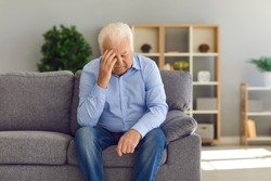 Tired, depressed senior man sitting on couch in living room feeling hurt and lonely. Aged, white-haired man touching forehead suffering from severe headache or recalling bad memories