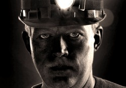 Tired dirty face of coal miner in helmet with light. Detailed portrait of mine worker.