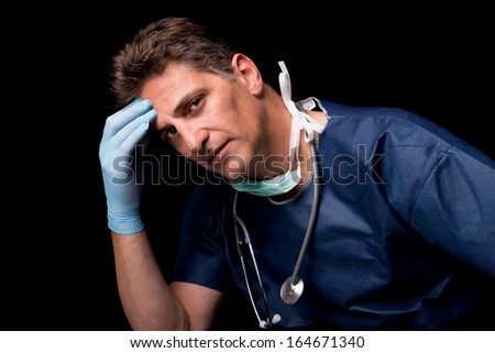 Tired doctor in uniform isolated against a black background #164671340