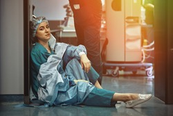 Tired doctor sitting after surgery in the hospital corridor. Great burden on doctors and medicine. Rest after work. Epidemic, pondemic lack of medical personnel.