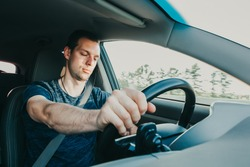 Tired driver falls asleep while driving car. Sleepy man wearing seat belt in vehicle. Risk of accident due to alcoholic intoxication. Unsafe driving from fatigue or drunkenness.