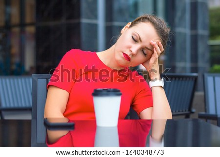 Tired exhausted girl, young beautiful woman sleeping in a cafe outdoors with a cup of coffee. Deadline, overworked and sleep deprivation, monday morning concept. Take a nap, snooze. Headache, migraine Stock photo ©