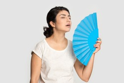 Tired exhausted Indian girl waving blue paper fan standing isolated on grey background, suffering from heat, sweaty young woman cooling in hot summer weather, high temperature, close up