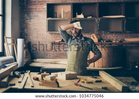 Tired exhausted weary overworked handsome bearded dressed in checkered shirt apron and gloves master of handmade crafts is wiping the sweat from his forehead, he is going to sell out his diy