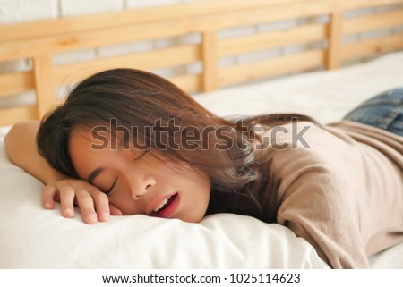 tired exhausted woman resting, woman sleeping and snoring; concept of overwork, exhausted, tired, sick, restless, stressed, recovered, resting, sleeping, lying down woman in home bedroom environment
