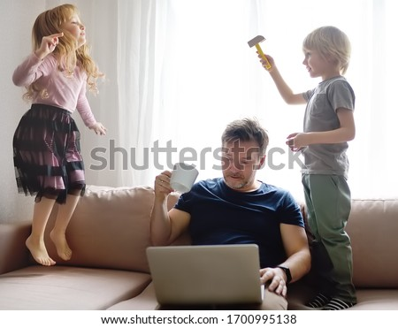 Tired father with his two kids during quarantine. Stay at home concept. Online working and household at the same time while quarantine. Exhausted parents with children.