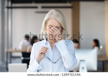Tired fatigued senior female employee taking off glasses massaging nose bridge feeling eye strain, middle aged office worker suffering from bad blurry vision loss, eyestrain tension problem symptoms