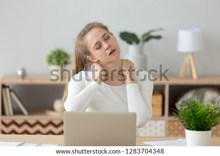 Tired fatigued young woman massaging stiff neck rubbing tensed muscles hurt to relieve back joint shoulder fibromyalgia pain after long sedentary computer work study in incorrect posture concept